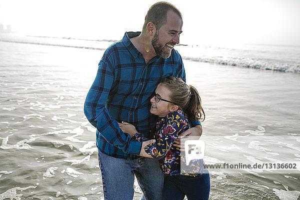 Fröhliche Vater und Tochter spielen im Meer am Strand