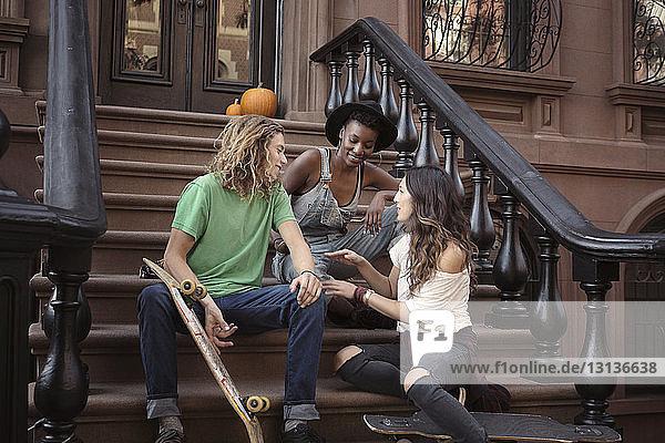 Freunde unterhalten sich im Sitzen mit Skateboards auf Stufen