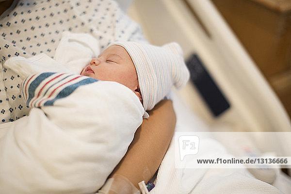 Hochwinkelansicht einer Mutter  die ein schlafendes Mädchen trägt