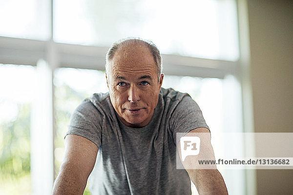 Älterer Mann beugt sich an einem sonnigen Tag zu Hause gegen das Fenster