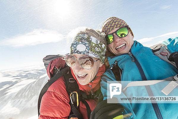 Glückliche Freundinnen mit Sonnenbrille und warmer Kleidung gegen den Himmel