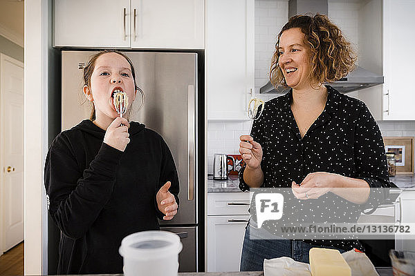 Mother looking at daughter tasting batter in kitchen