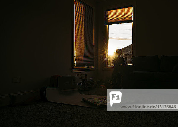 Silhouette of boy looking through window at home