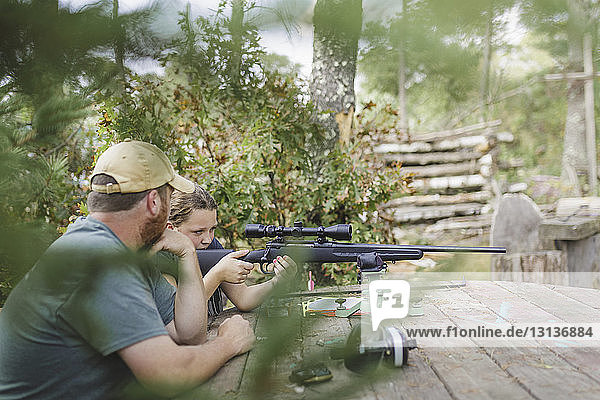 Father looking at daughter target shooting at backyard seen through plants
