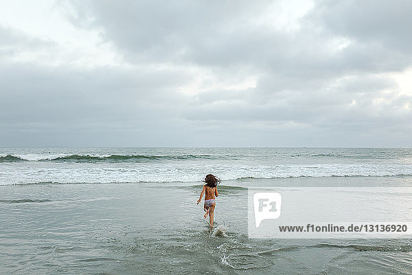Rear view of shirtless girl running towards sea against cloudy sky at beach