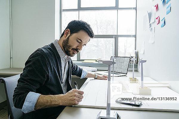 Geschäftsmann  der im Büro an Modellen von Windkraftanlagen arbeitet