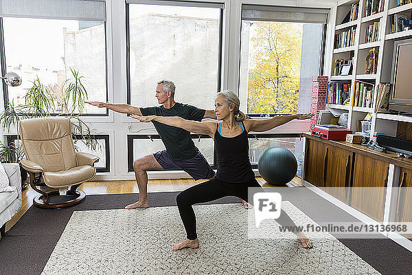 Full length of couple with arms outstretched and legs apart exercising at home