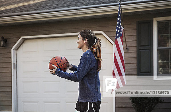Side view of woman holding basketball while standing at backyard