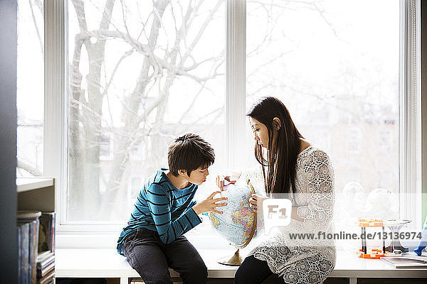 Mother and son looking at globe against window at home
