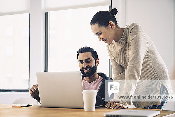 Smiling colleagues looking at laptop computer while discussing in office