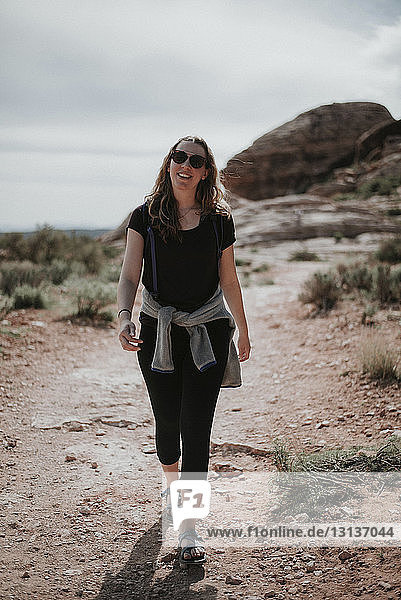 Female hiker in sunglasses walking on field at Red Rock Canyon National Conservation Area