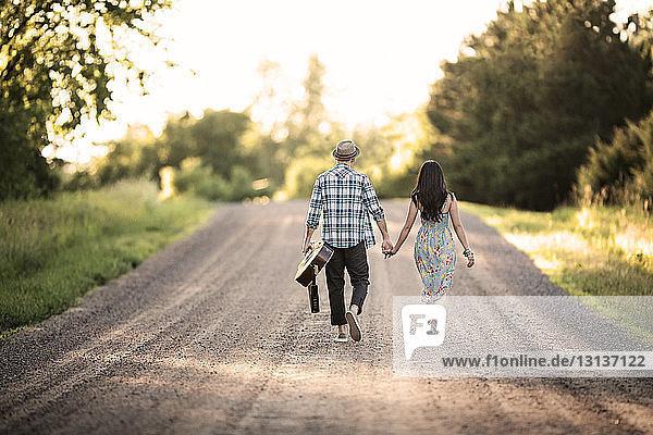 Rückansicht eines Paares  das an einem sonnigen Tag Händchen hält und an der Straße geht