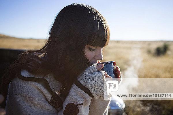 Frau trinkt Wasser  während sie auf einem Pick-up sitzt