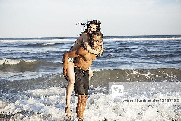 Ehepaar genießt Huckepack-Ritt am Ufer gegen das Meer