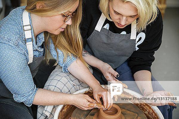 Frauen arbeiten in der Werkstatt an der Töpferscheibe