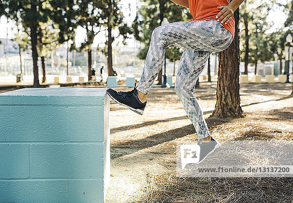 Low section of female athlete jumping on small blue column at park