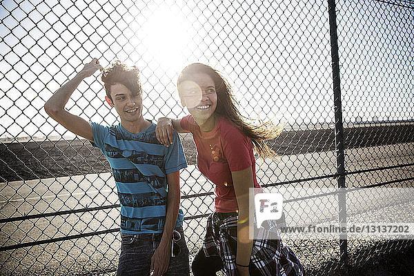 Lächelnde Freunde stehen am sonnigen Tag am Zaun gegen die Straße