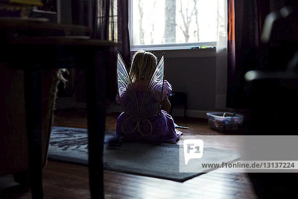 Rear view of girl in fairy costume sitting on floor at home