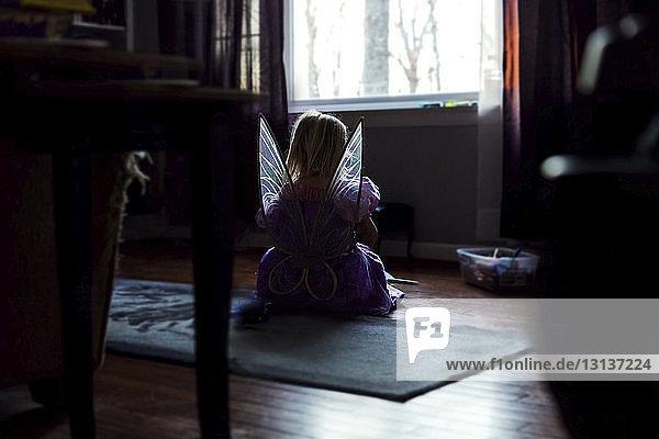 Rückansicht eines Mädchens im Feenkostüm  das zu Hause auf dem Boden sitzt