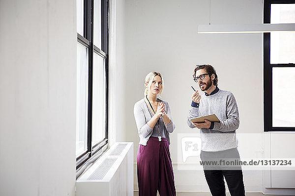 Immobilienmaklerin erklärt Geschäftsfrau den neuen Büroraum