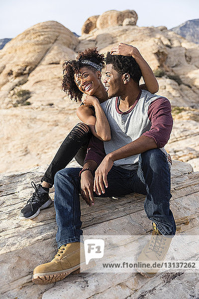 Happy couple sitting on rock formation