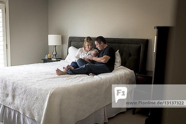 Eltern mit Sohn entspannen sich zu Hause im Bett