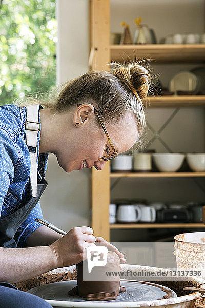 Seitenansicht einer Frau  die im Workshop an Steingut arbeitet