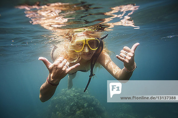 Woman gesturing while swimming in sea