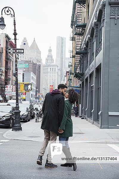 Geschäftspaar in voller Länge küsst sich stehend auf der Straße in der Stadt