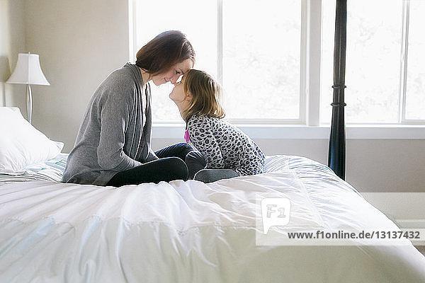 Verspielte Mutter mit Tochter zu Hause im Bett