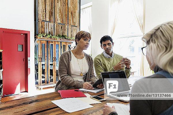Geschäftskollegen bei Besprechung am Konferenztisch im Büro