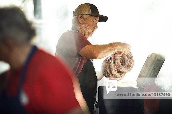 Mann beim Wurstmachen mit einem Mitarbeiter in der Küche