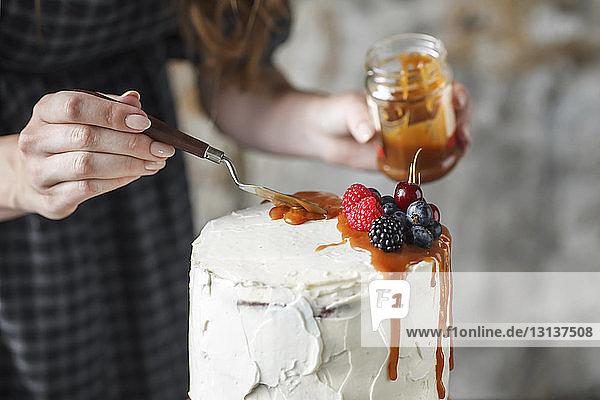 Mittelteil einer Frau  die zu Hause einen Kuchen mit Karamell und Beerenfrüchten glasiert