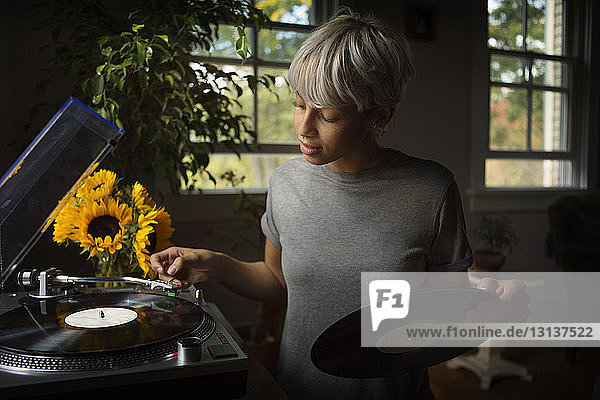 Frau legt zu Hause Vinyl-Schallplatte auf den Plattenteller