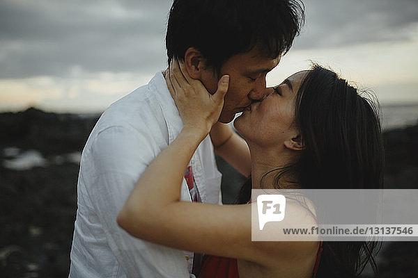 Nahaufnahme eines Paares  das sich bei Sonnenuntergang am Strand gegen den Himmel küsst