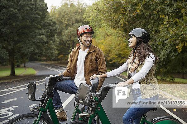 Lächelndes Paar unterhält sich im Stehen mit Fahrrädern auf der Straße im Park