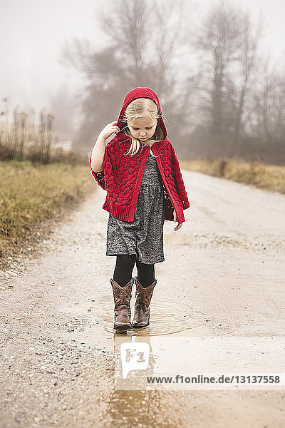Girl in warm clothing walking on puddle