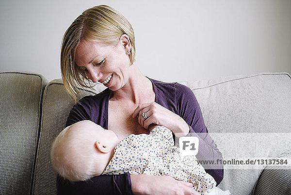 Lächelnde Frau  die ihre Tochter stillt  während sie zu Hause auf dem Sofa sitzt