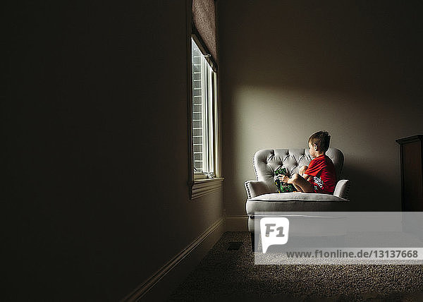 Boy playing with toy car while sitting on armchair at home