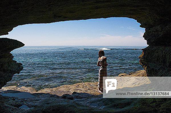 Rückansicht einer jungen Frau  die auf einem felsigen Ufer steht  durch eine Höhle