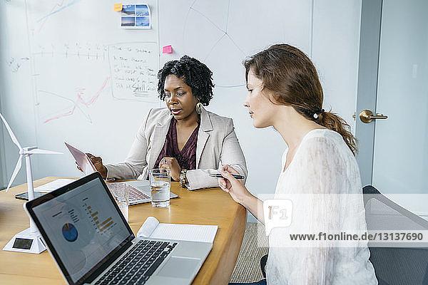 Geschäftsfrauen diskutieren über Laptop-Computer im Sitzungssaal