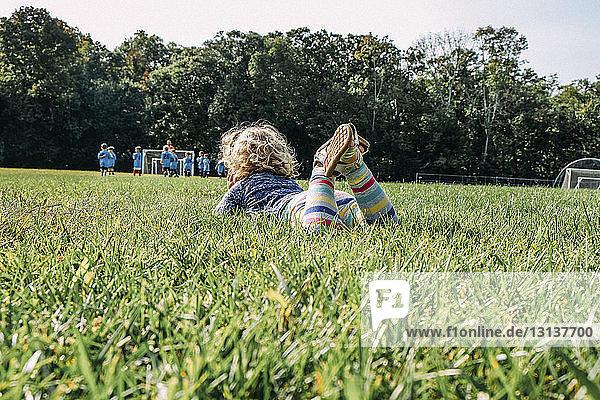 Mädchen sieht sich ein Fußballspiel an  während sie auf dem Rasen eines Spielplatzes liegt