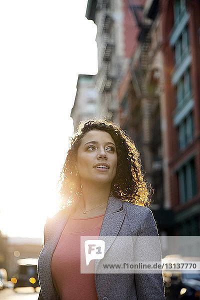 Nachdenkliche Geschäftsfrau schaut weg  während sie auf der Straße der Stadt steht