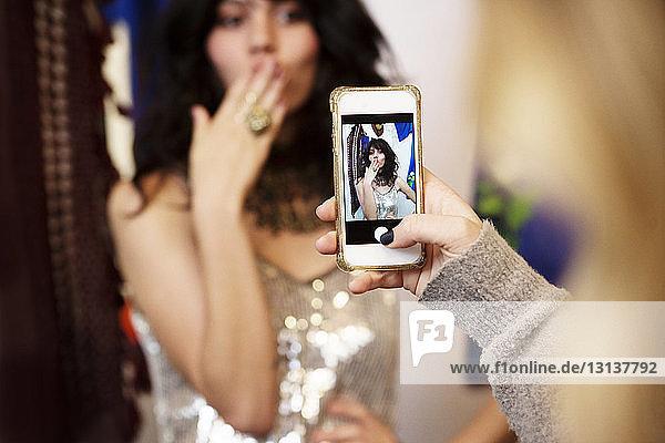 Ausschnitt einer Frau  die in einer Boutique die Besitzerin fotografiert