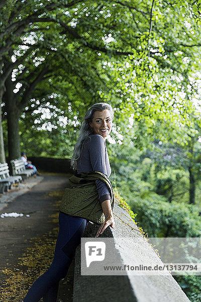 Lächelnde Frau schaut weg  während sie sich auf Stützmauer gegen Bäume stützt