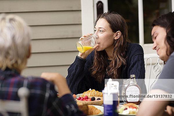 Frau schaut weg  während sie mit Freunden am Frühstückstisch Orangensaft trinkt