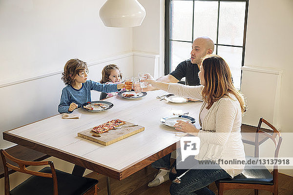Family raising celebratory toast while sitting at dining table in home