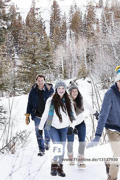 Glückliche Familie beim Spaziergang auf verschneitem Feld