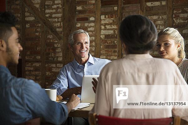 Lächelnder Geschäftsmann hört Kollegen während eines Treffens im Café zu