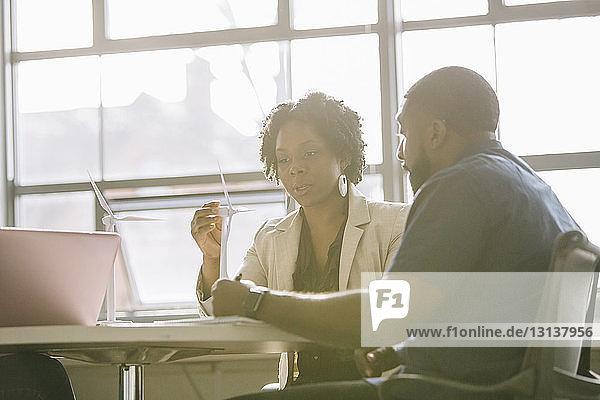 Geschäftsleute diskutieren über Windkraftanlagenmodelle  während sie im Büro am Tisch sitzen